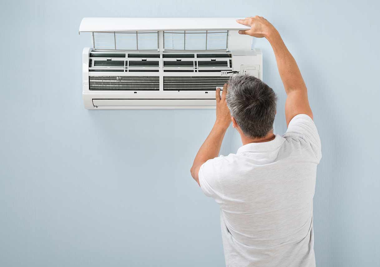 man inspecting air conditioning unit