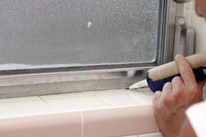 Man applying caulk to a window frame