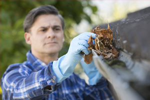 Man using gloves to clean gutters
