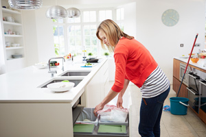 Woman cleans out kitchen garbage can