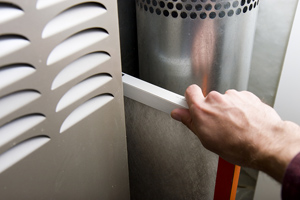 hand changing home furnace filter