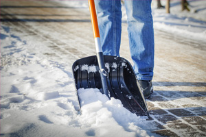 man with snow shovel clearing brick sidewalk