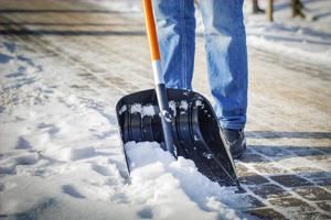 man with snow shovel clearing brick sidewalk