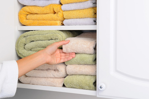 Person organizing towels in bathroom closet