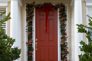 red door decorated with Christmas garland and poinsettias