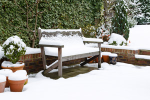 snow-covered patio bench and pots