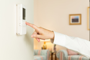 white hand pressing button on thermostat