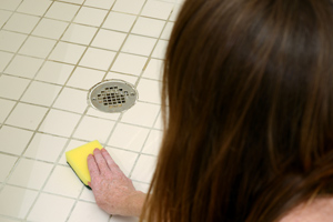 woman scrubbing shower with pad