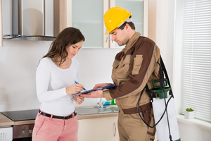 woman signing paper with exterminator in kitchen
