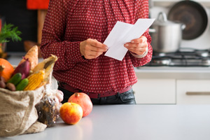 woman with shopping list in kitchen